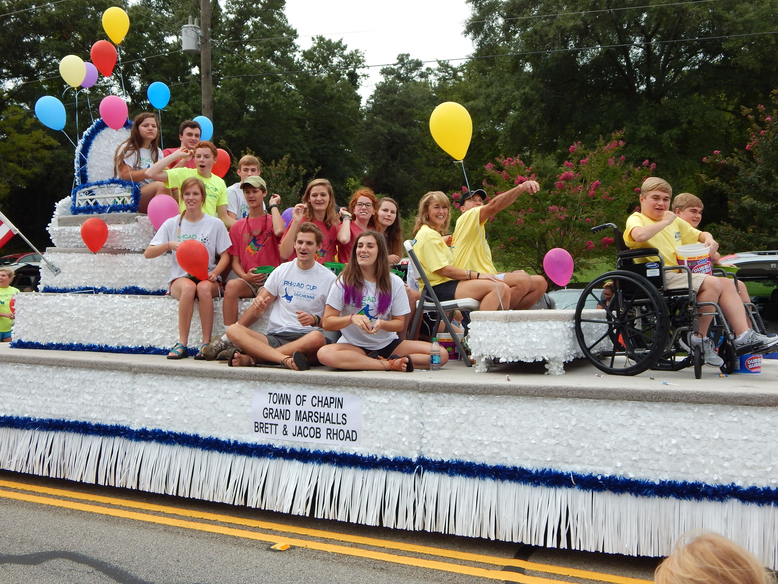 Young people riding on a parade float.